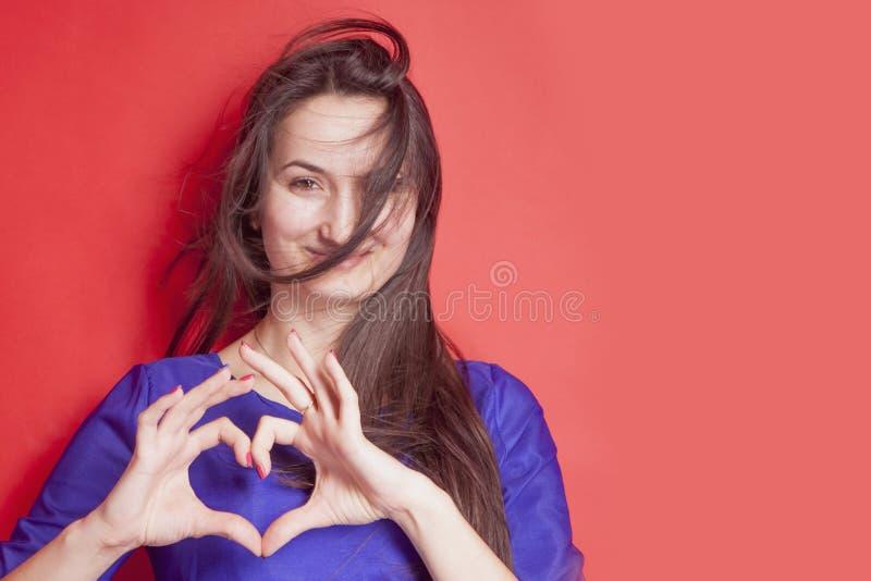 Concept: De liefde is blind Portret van vrij romantische jonge vrouw die een hartgebaar met haar vingers maken tegen rode achterg royalty-vrije stock afbeelding
