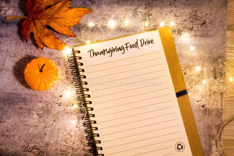 Concept de liste d'entraînement de nourriture de thanksgiving sur le carnet entouré avec les feuilles lumineuses et les lumières  photographie stock libre de droits