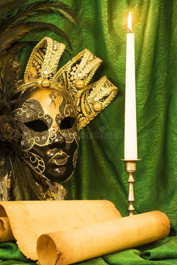 Concept de littérature, bougie dans un chandelier près d'un masque vénitien photo stock