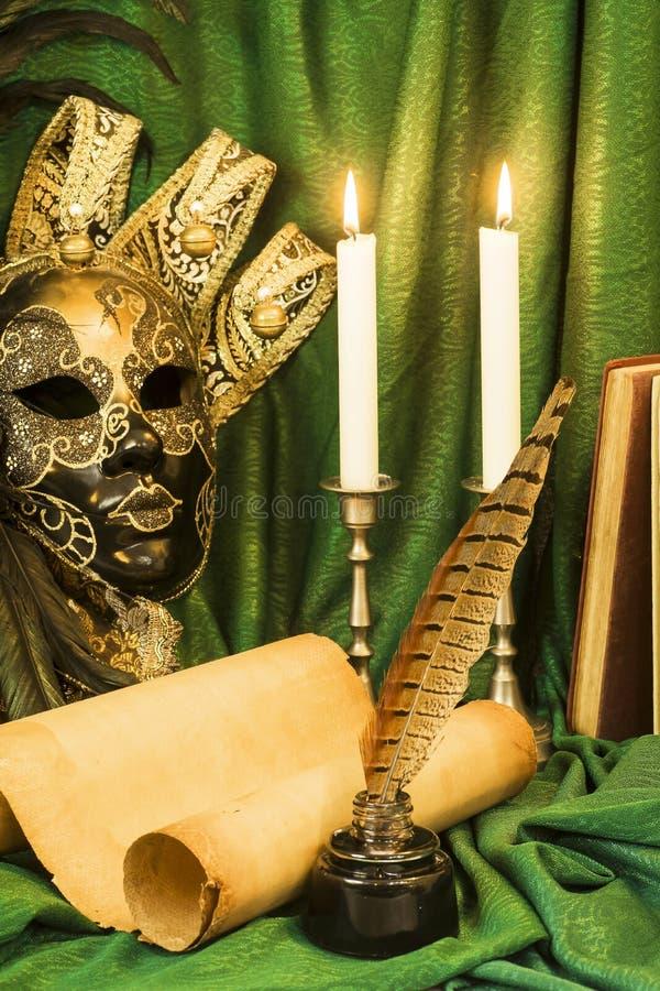 Concept de littérature, bougie dans un chandelier près d'un masque vénitien image stock