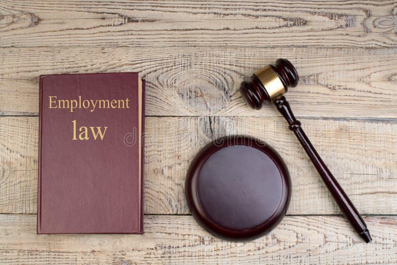 Concept de loi - droit de l'emploi Livre de loi ouvert avec un marteau en bois de juges sur la table dans une salle d'audience ou photographie stock libre de droits