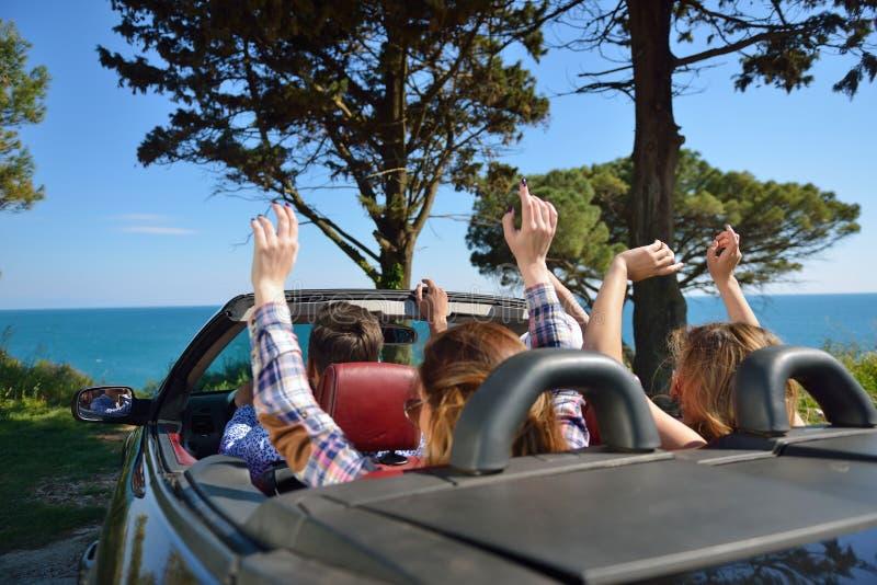 Concept de loisirs, de voyage par la route, de voyage et de personnes - amis heureux conduisant dans la voiture de cabriolet le l photos stock