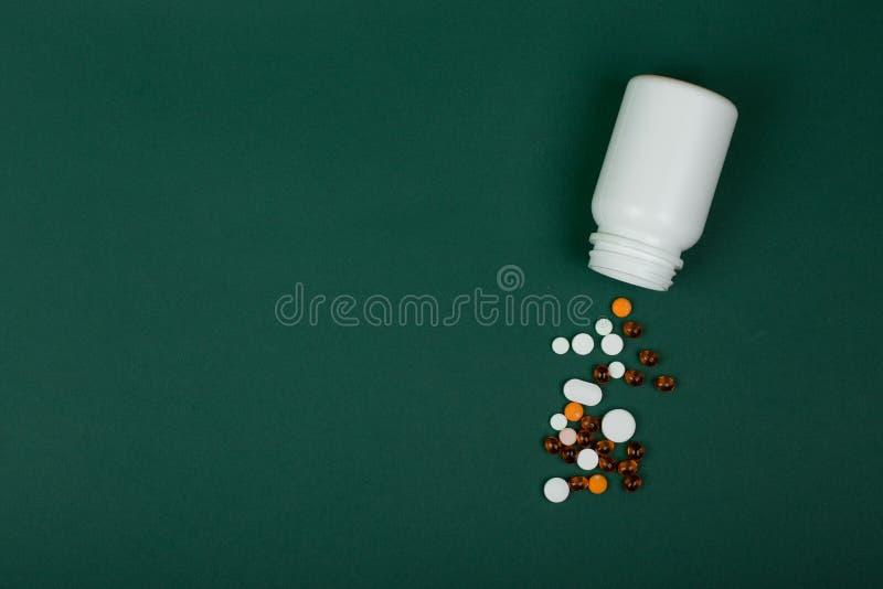 Concept de m?decine - pilules color?es et bouteille m?dicale blanche sur le fond de Livre vert photos stock