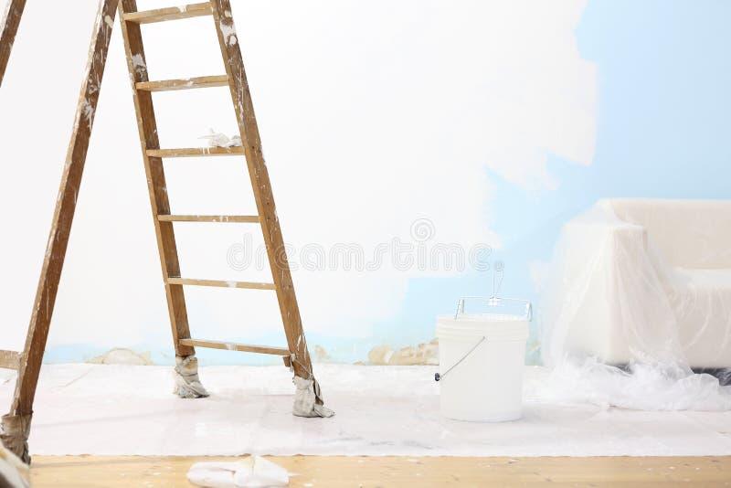 Concept de maison de peintre, échelle en bois, seau, et mur blanc image libre de droits
