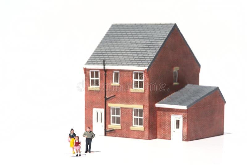 Concept de maison familiale avec la maison et les personnes modèles sur le backgro blanc image libre de droits