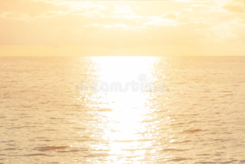 Concept de mer d'aube : Fond de texture de coucher du soleil de lumière de Sun et de plage de tache floue photos libres de droits