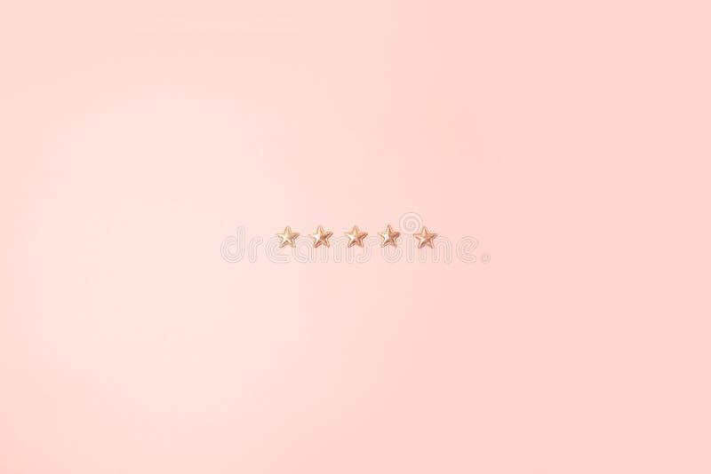 Concept de minimalisme Cinq formes brillantes roses d'étoiles sur le fond rose photos stock