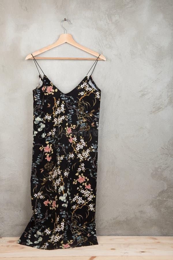 Concept de mode et d'achats - belle robe dans le modèle floral sur un cintre photographie stock