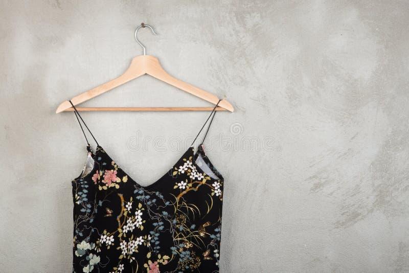 Concept de mode et d'achats - belle robe dans le modèle floral sur un cintre photographie stock libre de droits