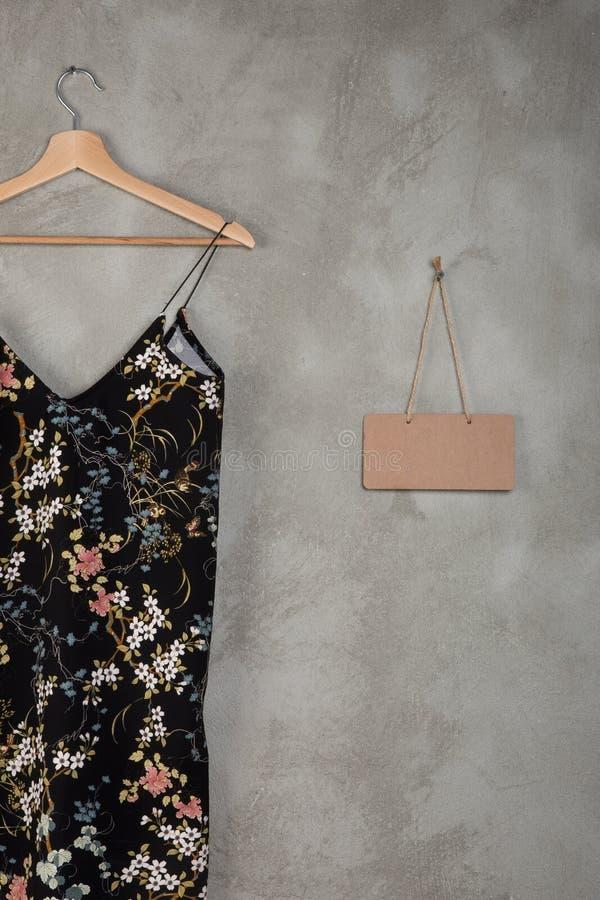 Concept de mode et d'achats - tableau noir vide et belle robe dans le modèle floral sur un cintre images stock