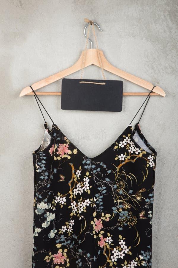 Concept de mode et d'achats - tableau noir vide et belle robe dans le modèle floral sur un cintre image libre de droits