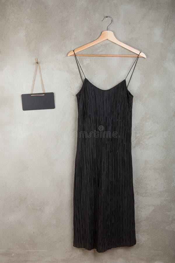 Concept de mode et d'achats - tableau noir vide et belle robe noire sur un cintre photographie stock