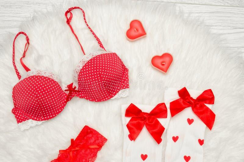 Concept de mode Soutien-gorge rouge et bas blancs avec les arcs, bougies sous forme de coeur sur une fourrure blanche Vue supérie image stock