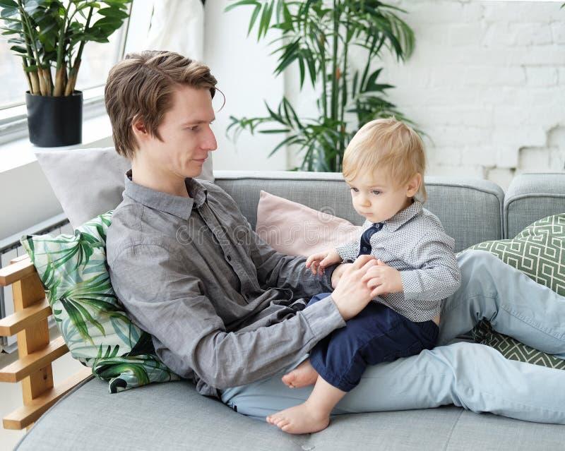 Concept de mode de vie, de famille et de personnes - jeune p?re heureux avec son fils d'un an jouant ? la maison images stock