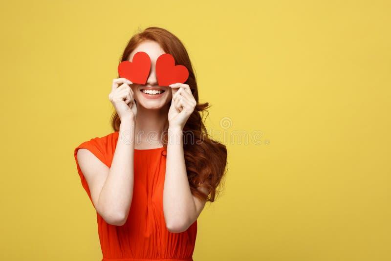 Concept de mode de vie : Femme attirante avec le sourire de lancement ayant deux petits coeurs rouges dans des mains, yeux ferman image stock