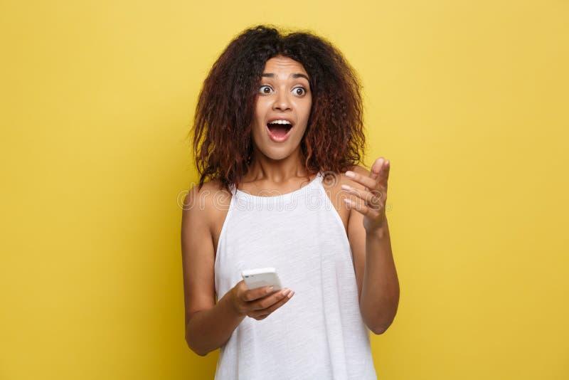 Concept de mode de vie - le portrait de beau choquer de femme d'Afro-américain voient quelqu'un et tenant le téléphone portable j images stock