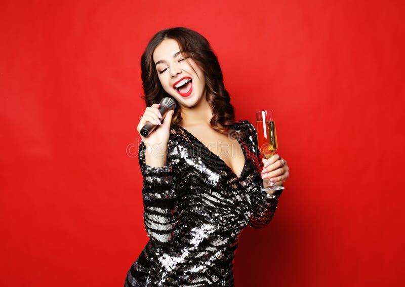Concept de mode de vie, de partie et de personnes : belle fille dans une robe de cocktail tenant un verre de champagne et de micr photos stock