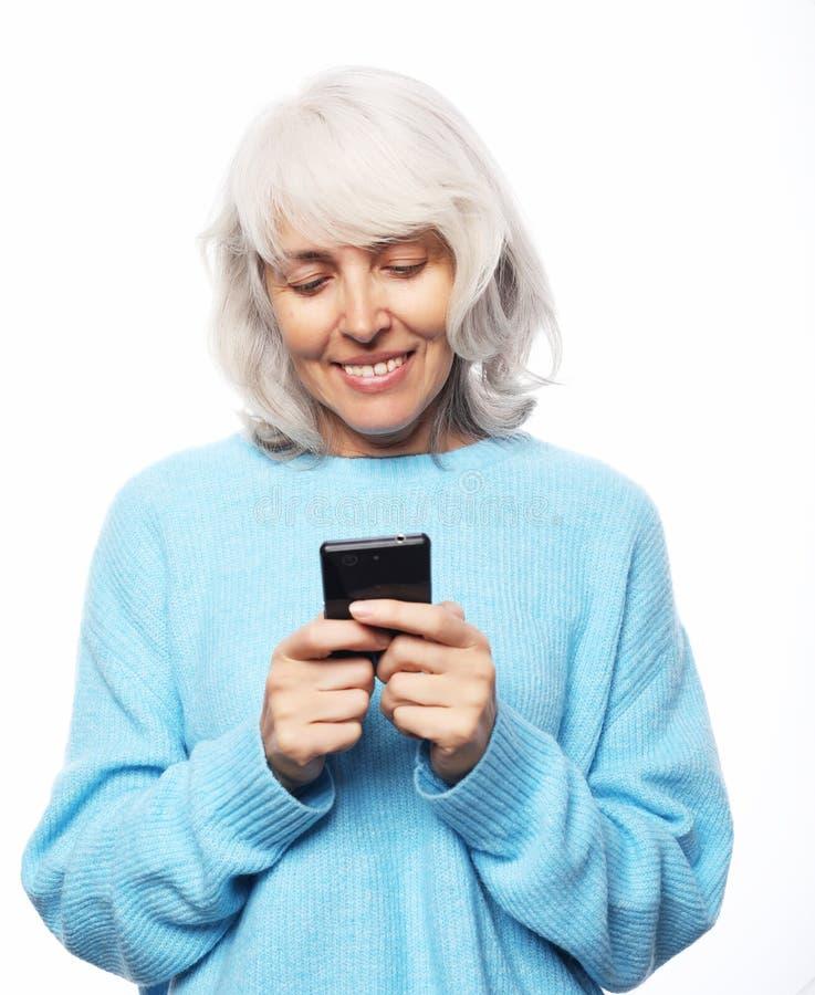 Concept de mode de vie, de tehnology et de personnes : dame ?g?e portant parler occasionnel au t?l?phone portable au-dessus du fo photographie stock libre de droits