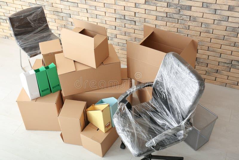 Concept de mouvement de bureau Boîtes et chaises de carton sur le plancher photo libre de droits