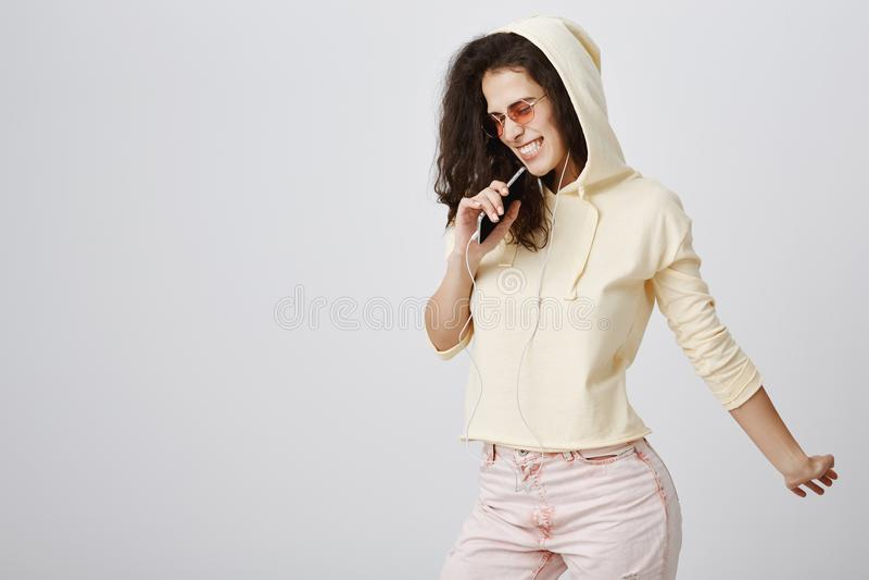 Concept de musique et de mode de vie Fille urbaine belle joyeuse avec les cheveux bouclés utilisant l'équipement à la mode et l'e image libre de droits
