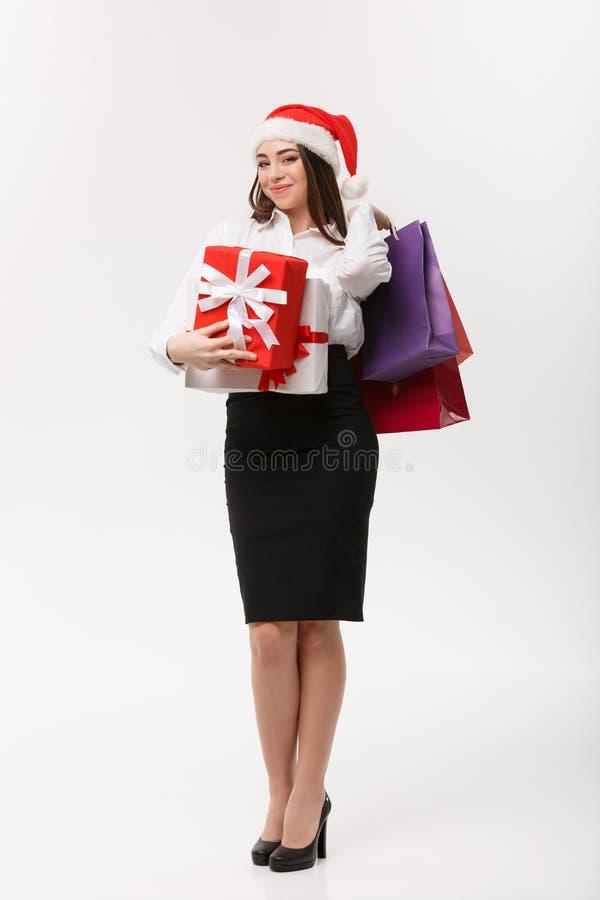 Concept de Noël - belle femme d'affaires tenant les paniers et le présent avec l'espace de copie images libres de droits