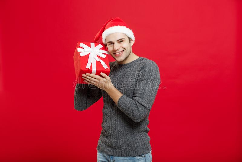 Concept de Noël - jeune homme beau dans le chandail avec le cadeau rouge de Noël image libre de droits