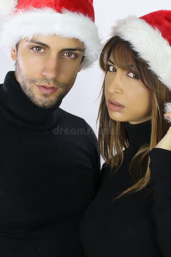 Concept de Noël Jeunes couples attrayants utilisant un chapeau de Santa photos stock