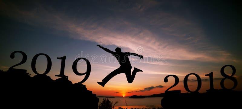 Concept 2019 de nouvelle année de l'homme de voyage de silhouette sautant sur le Cl photos stock
