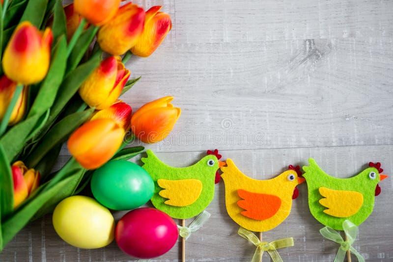 Concept de Pâques - fin des oeufs colorés, des poussins décoratifs et des tulipes au-dessus de la table en bois photos libres de droits