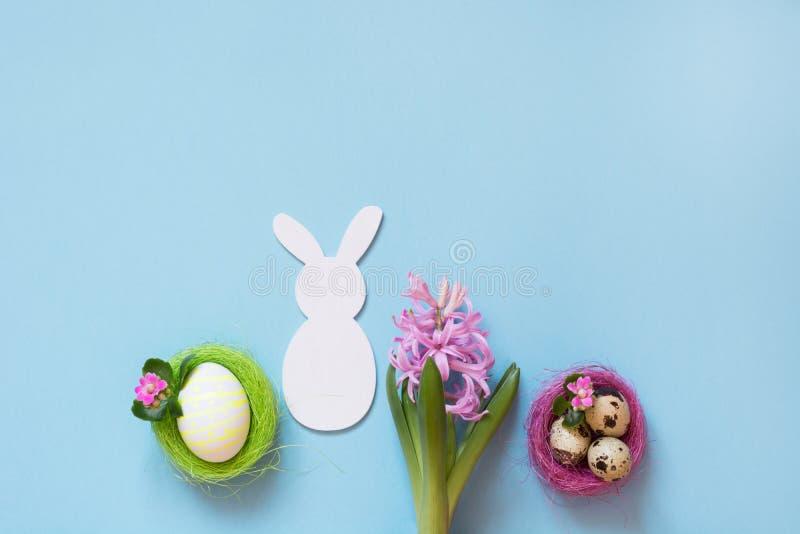 Concept de Pâques Le lapin blanc et le poulet peint eggs avec le décor de fleur sur le bleu Vue supérieure Configuration plate images stock
