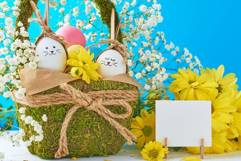 Concept de Pâques Oeufs dans le panier décoré des fleurs sur un fond bleu photo libre de droits