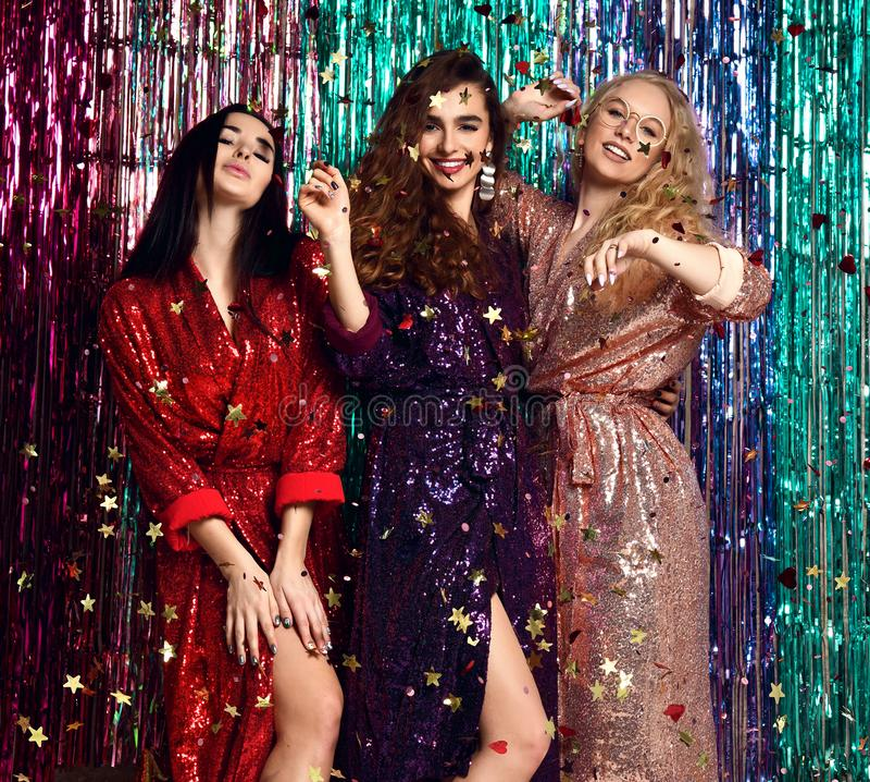 Concept de partie et de vacances Trois femmes de charme dans les paillettes de luxe de scintillement habillent avoir l'amusement photographie stock libre de droits