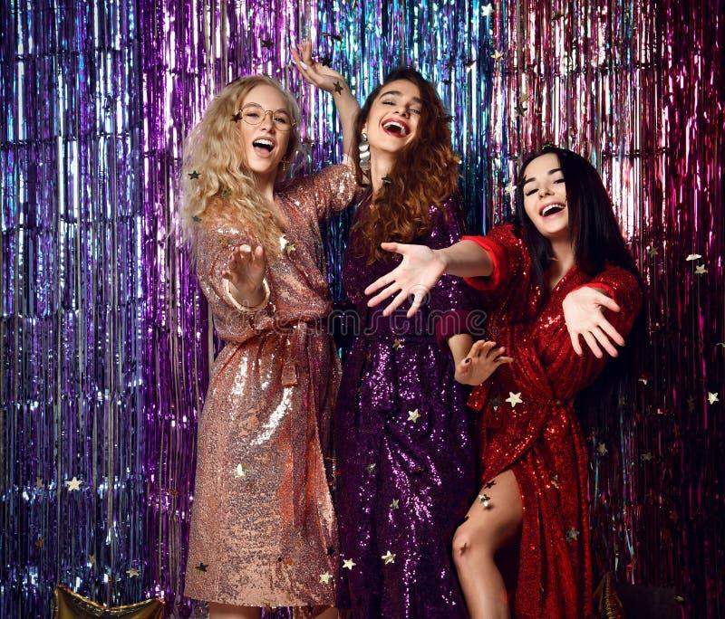 Concept de partie et de vacances Trois femmes de charme dans les paillettes de luxe de scintillement habillent avoir l'amusement photographie stock