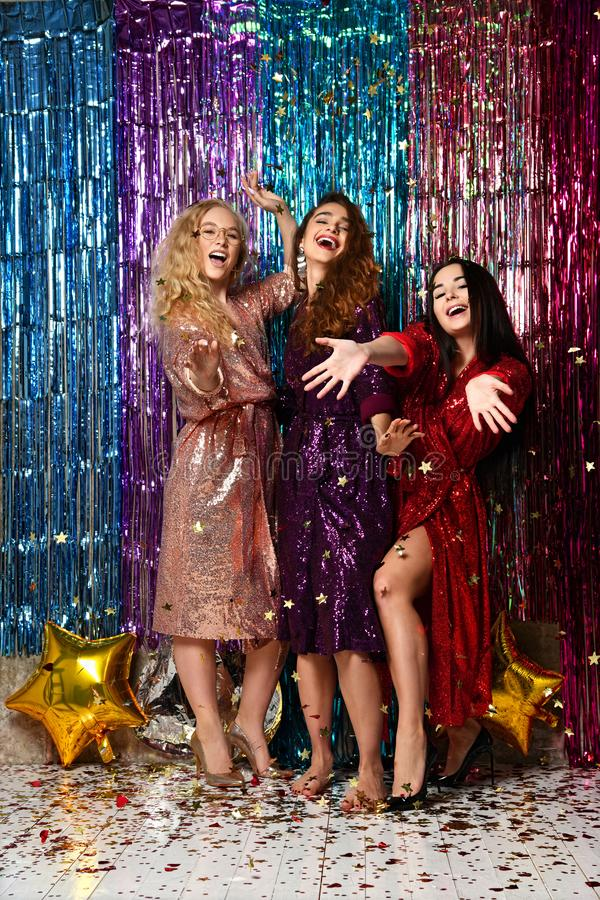 Concept de partie et de vacances Trois femmes de charme dans les paillettes de luxe de scintillement habillent avoir l'amusement photos libres de droits