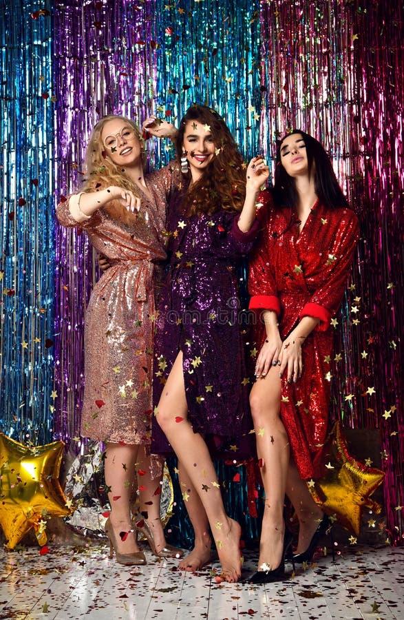 Concept de partie et de vacances Trois femmes de charme dans les paillettes de luxe de scintillement habillent avoir l'amusement photo libre de droits