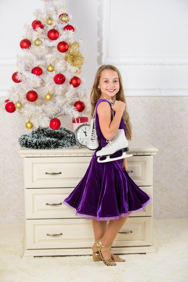 Concept de patinage artistique L'enfant près de la prise d'arbre de Noël patine cadeau Peu cadeau satisfaisant de Noël de fille L photo stock