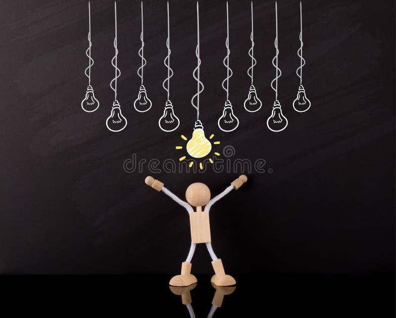 Concept de pensée critique de qualifications, bras en bois de chiffre de bâton, grand croquis jaune d'ampoule, sur un tableau photo stock