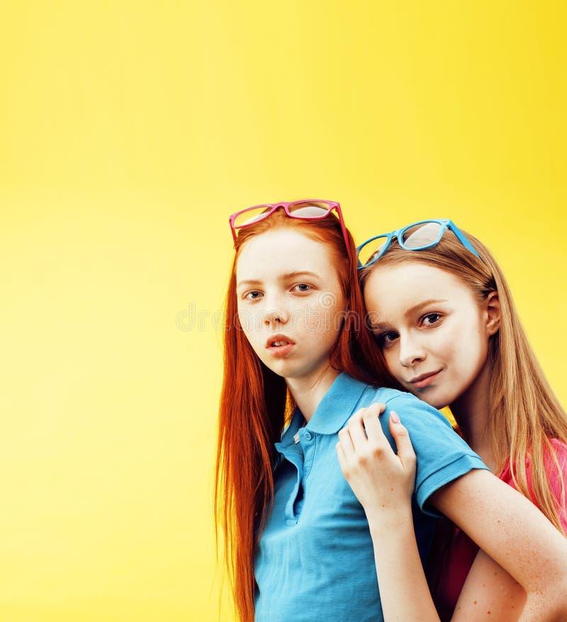 Concept de personnes de mode de vie : deux adolescentes assez jeunes d'école ayant le sourire heureux d'amusement sur le fond jau image stock