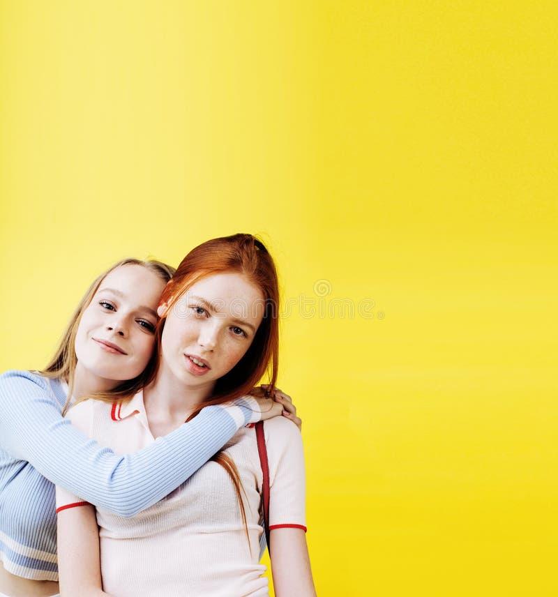 Concept de personnes de mode de vie : deux adolescentes assez jeunes d'école ayant le sourire heureux d'amusement sur le fond jau images libres de droits
