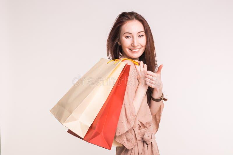 Concept de personnes, de vente et de consommationisme - femme asiatique heureuse au-dessus du fond blanc tenant des paniers photos stock