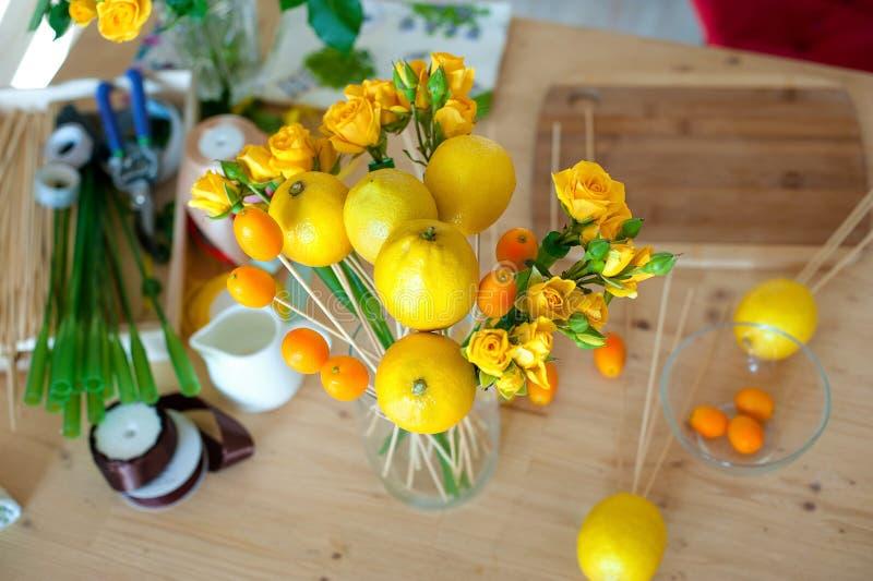 concept de petite entreprise Procédé de travail de bouquet de fleuriste de fruit et de fleurs Bouquet jaune en emballage bleu images libres de droits