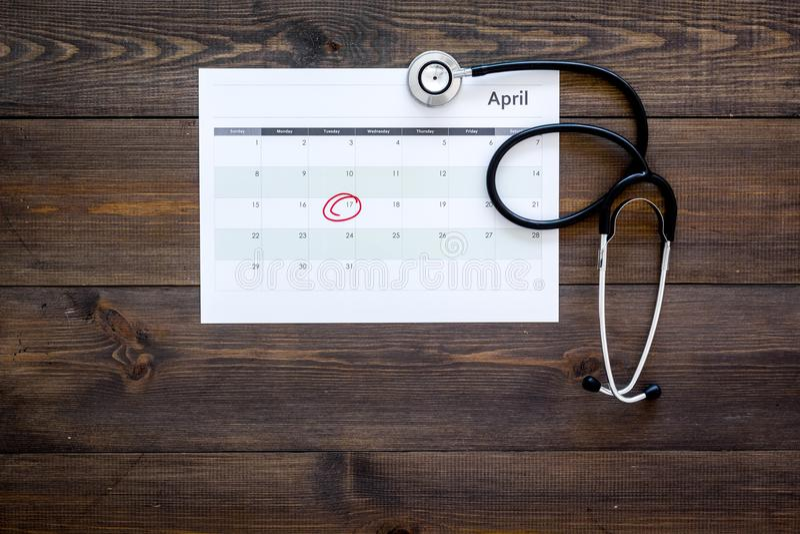 Concept de planification d'examen médical Examens médicaux réguliers Calendrier avec la date cerclée et stéthoscope sur l'obscuri images libres de droits
