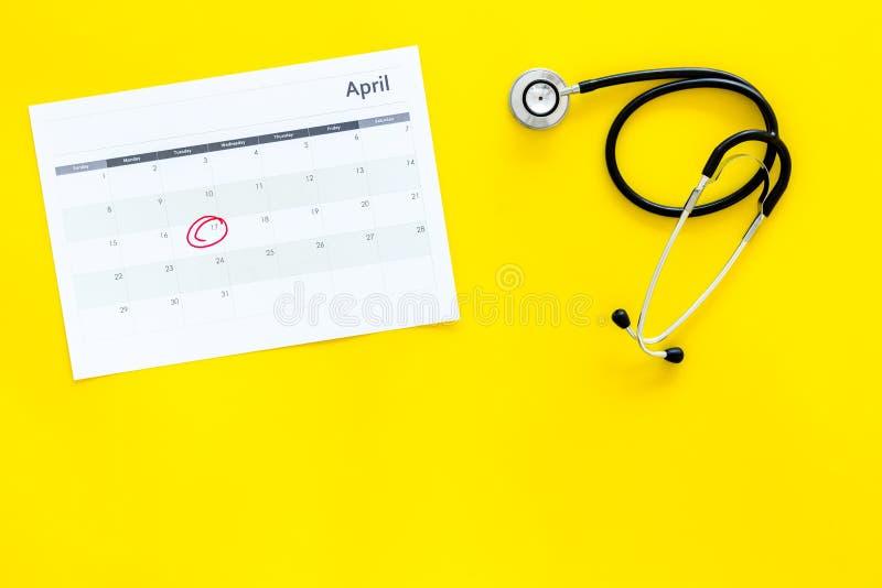 Concept de planification d'examen médical Examens médicaux réguliers Calendrier avec la date cerclée et stéthoscope sur le jaune photographie stock
