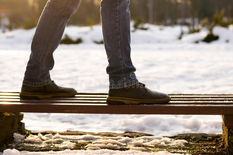 Concept de prendre la décision, début, solitude Les jambes masculines de plan rapproché dans les bottes et des blues-jean brunes  photographie stock