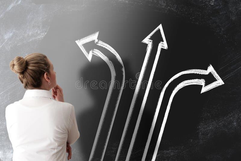 Concept de prise de décision avec la vue arrière de la femme regardant le tableau avec des flèches se dirigeant dans différen photos stock