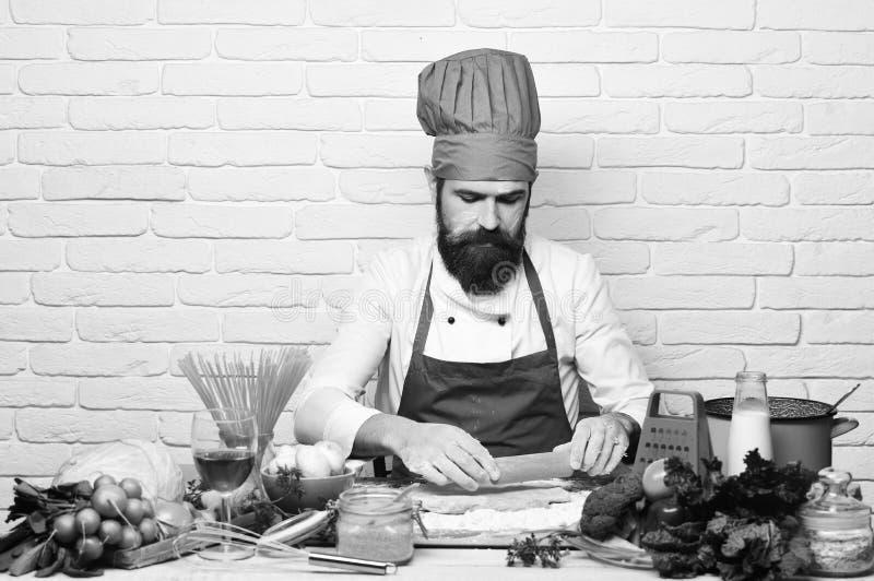 Concept de procédé de cuisson L'homme avec la barbe déroule la pâte sur le fond blanc de mur de briques Cuisinier avec le visage  photographie stock