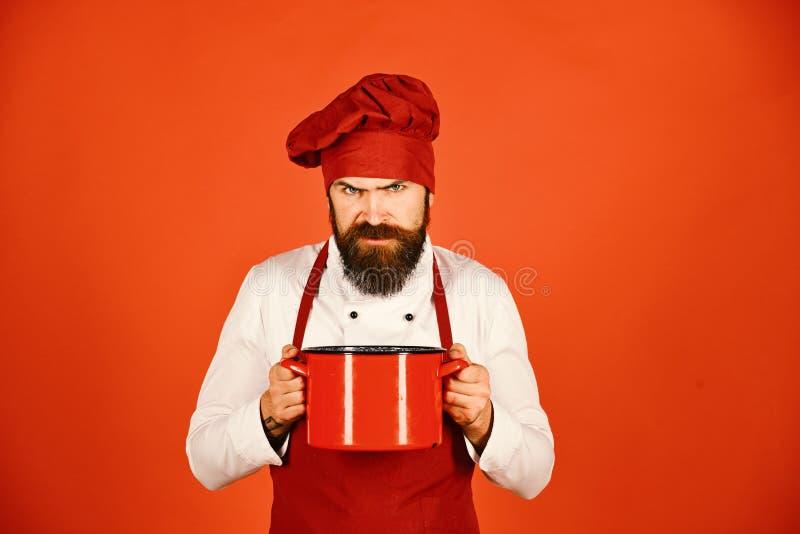 Concept de procédé de cuisson L'homme avec la barbe tient la vaisselle de cuisine photo libre de droits