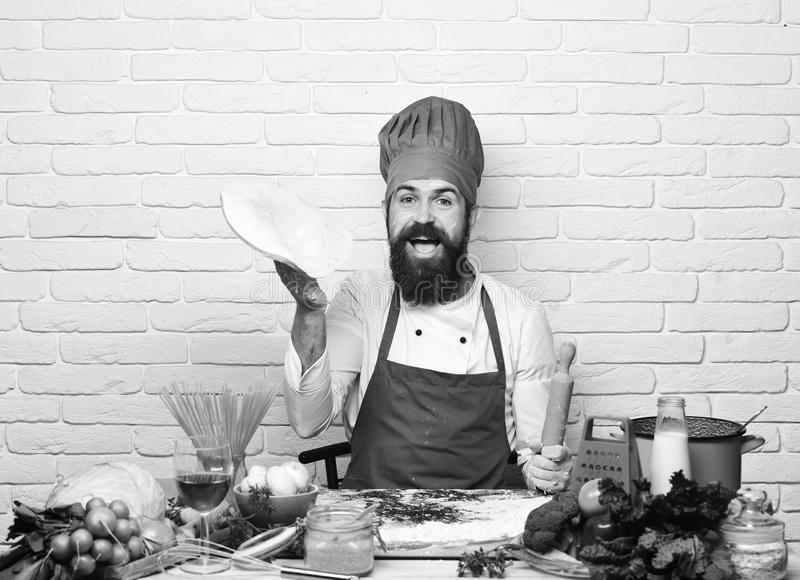 Concept de procédé de cuisson Le chef fait la pizza Le cuisinier avec le visage heureux dans l'uniforme de Bourgogne s'assied par photos libres de droits