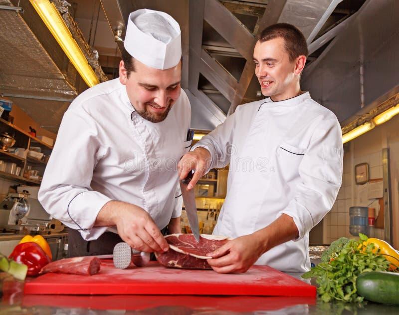 Concept de procédé de cuisson Portrait de deux ouvriers en nourriture de fabrication uniforme de cuisinier dans la cuisine modern images libres de droits