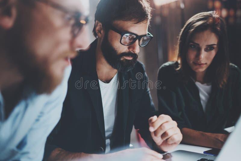 Concept de procédé de travail d'équipe au bureau Jeune équipe travaillant ensemble au grenier moderne de bureau de nuit Fond brou image stock